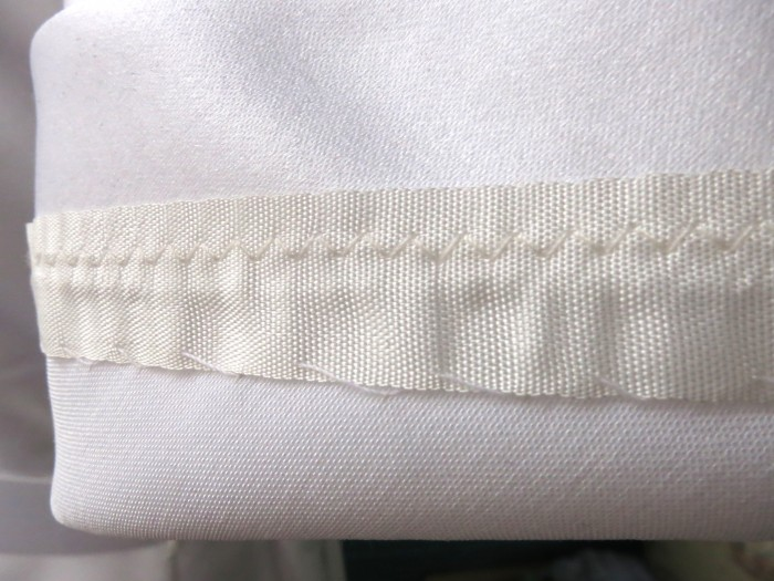 Rayon tape to hem sleeves. Less scratchy than the lace.