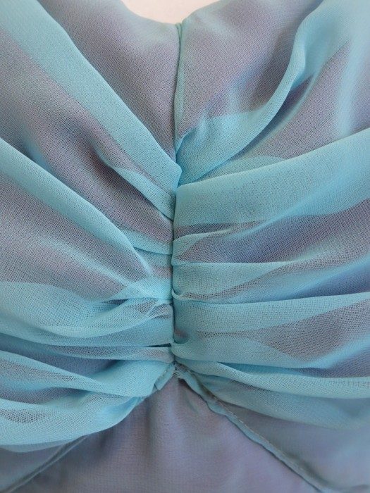 Draped bodice pleats.