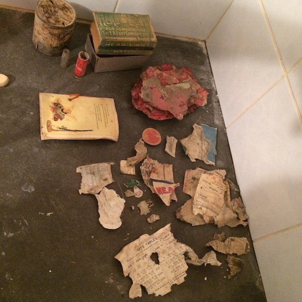 Treasures found under the stairs. Lots of paper fragments and a bunch of old grocery receipts!