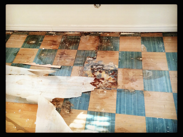 Damaged tile under the laminate in the upstairs bedrooms. So much scrubbing!